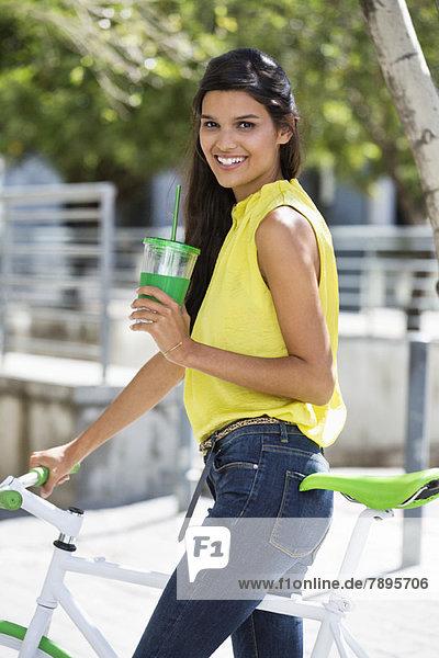 Porträt einer Frau auf dem Fahrrad sitzend und trinkend