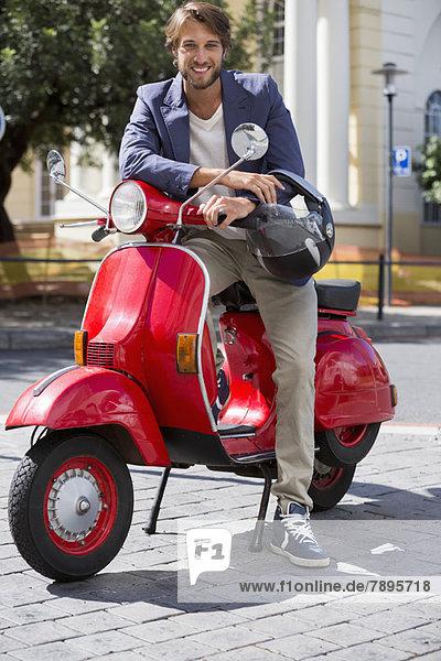 Porträt eines Mannes auf einem Roller sitzend und lächelnd