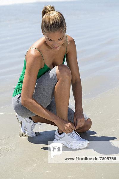 Frau  die ihre Schnürsenkel am Strand bindet