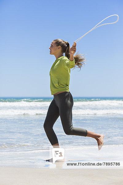 Springseil der Frau am Strand