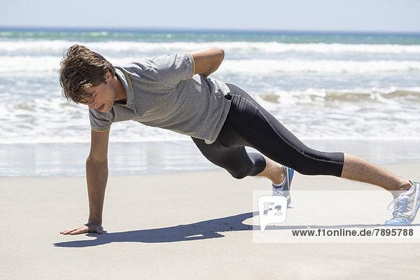 Mann trainiert am Strand