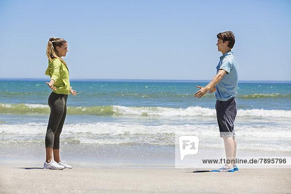 Frau beim Training am Strand mit ihrem Trainer