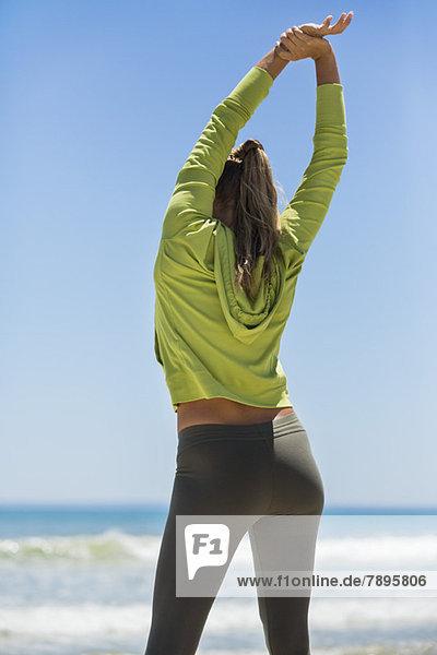 Rückansicht einer am Strand trainierenden Frau