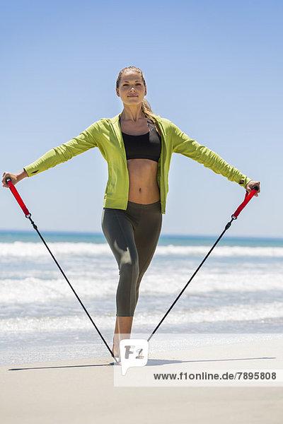 Frau beim Training mit einem Brust-Expander am Strand
