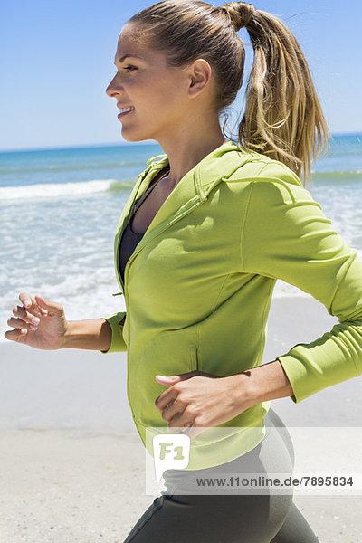 Lächelnde Frau beim Laufen am Strand
