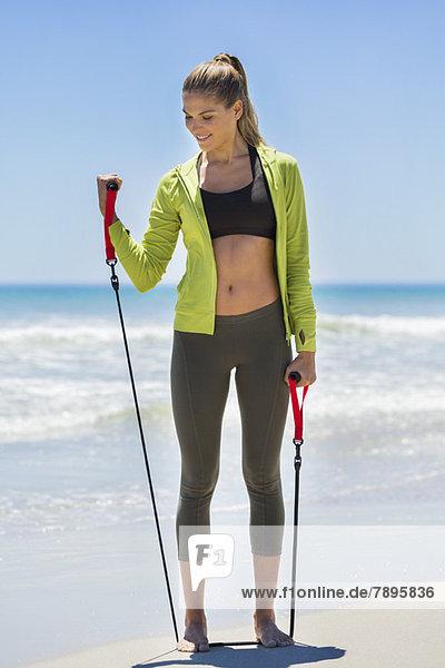 Frauenübung mit einem Brust-Expander am Strand
