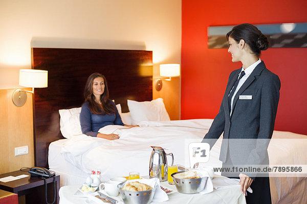 Kellnerin,  die einer Frau im Hotelzimmer Essen serviert.