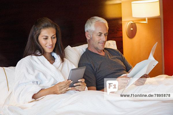 Frau  die ein digitales Tablett benutzt  während ihr Mann in einem Hotelzimmer ein Buch liest.