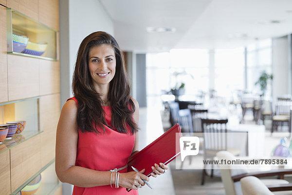 Porträt einer Kellnerin mit einer Akte in einem Restaurant Porträt einer Kellnerin mit einer Akte in einem Restaurant