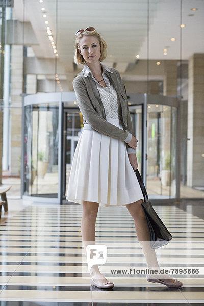 Frau steht auf einem Flughafen und hält eine Lederhandtasche.