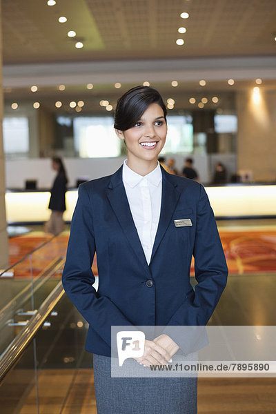Receptionist standing in a hotel lobby and smiling
