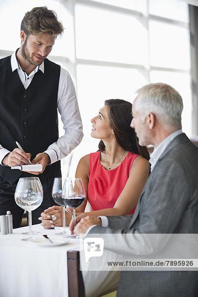 Kellner  der Bestellungen von einem Paar in einem Restaurant entgegennimmt. Kellner, der Bestellungen von einem Paar in einem Restaurant entgegennimmt.