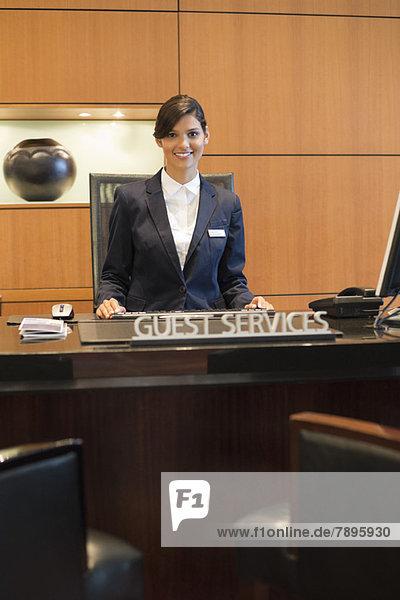 Porträt einer lächelnden Empfangsdame an der Hotelrezeption