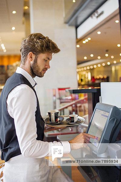Kellner mit Computer an der Kasse eines Restaurants