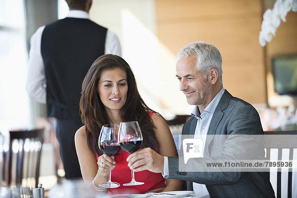 Pärchentoast mit Weingläsern im Restaurant