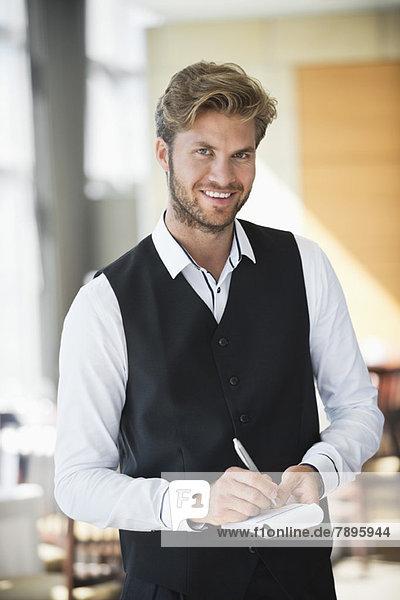 Porträt eines Kellners  der in einem Restaurant eine Bestellung aufnimmt.