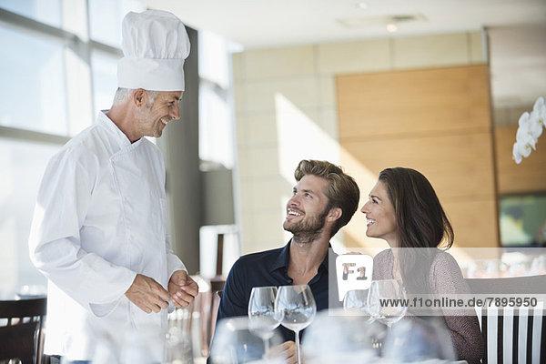Chefkoch im Gespräch mit einem Paar im Restaurant