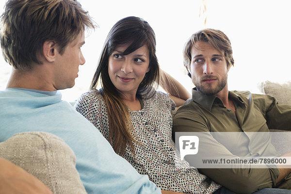 Drei Freunde sitzen zusammen auf einer Couch.