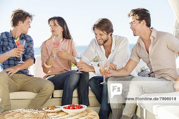 Gruppe von Freunden  die im Urlaub im Freien Getränke genießen.
