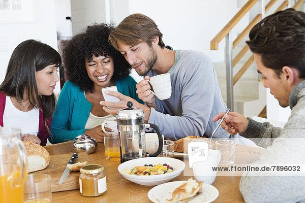 Freunde  die an einem Esstisch sitzen und ein Handy anschauen