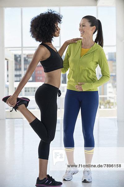 Instruktorin  die einer Frau im Fitnessstudio assistiert