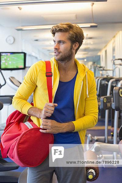 Mann mit Tasche im Fitnessstudio