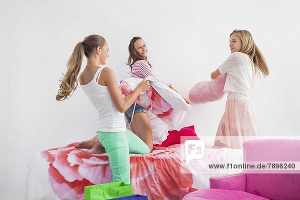 Mädchen mit Kissenschlacht auf dem Bett bei einer Pyjamaparty