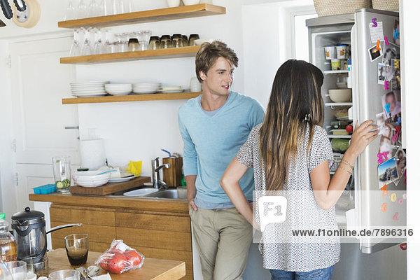 Frau schaut mit ihrem Mann in der Küche auf einen Kühlschrank.
