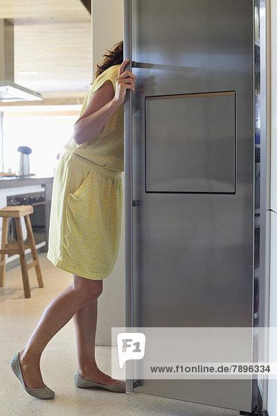 Frau schaut in einen Kühlschrank in der Küche