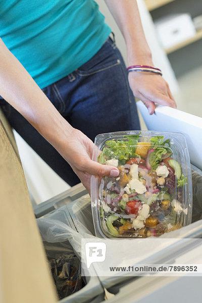 Frau wirft Müll in eine Mülltonne