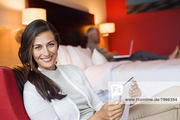 Frau mit einem digitalen Tablett im Hotelzimmer und ihr Mann mit Laptop im Hintergrund