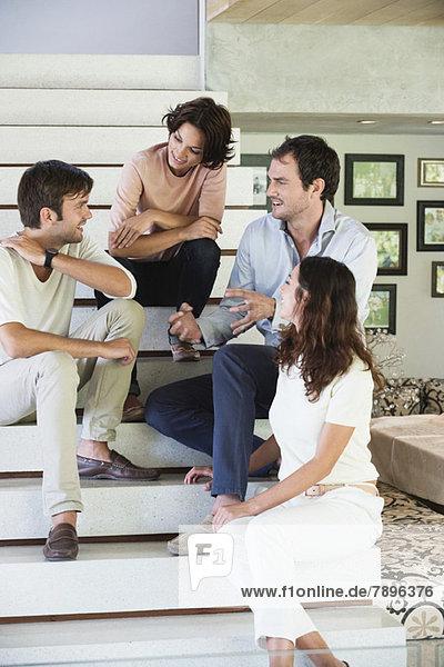 Lächelnde Freunde  die auf Stufen sitzen und miteinander reden.