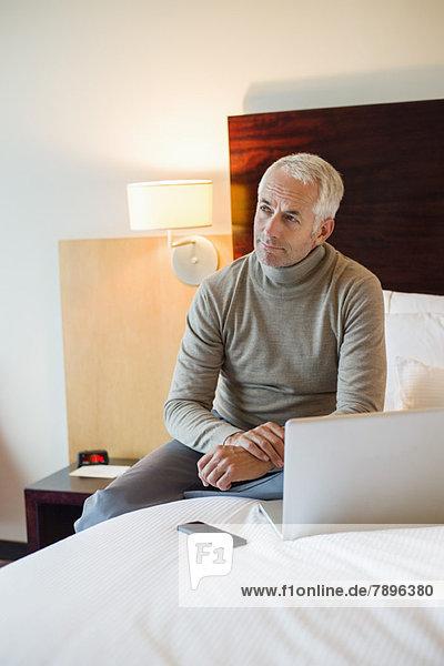 Mann mit Laptop im Hotelzimmer