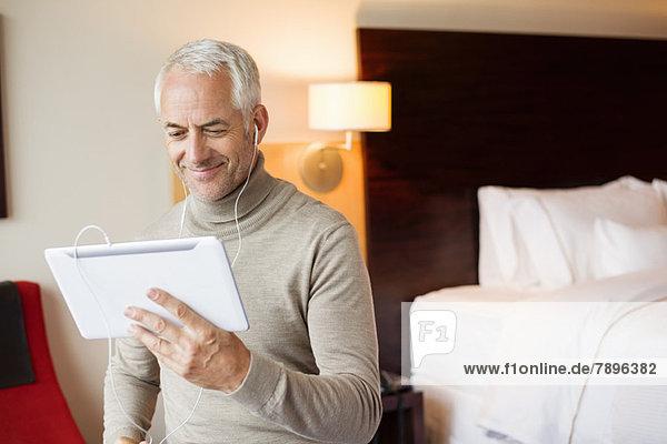 Mann  der sich einen Film auf einem digitalen Tablett in einem Hotelzimmer ansieht.
