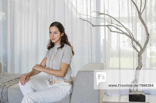 Schöne Frau auf einer Couch sitzend