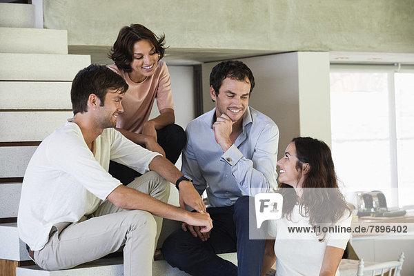Lächelnde Freunde auf der Treppe sitzend