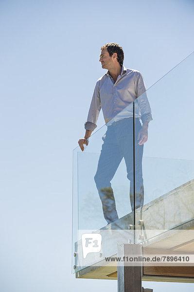 Mann steht auf der Terrasse und schaut weg.