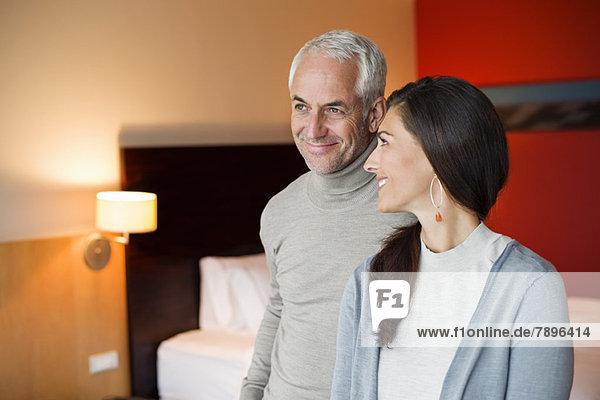 Paar lächelt in einem Hotelzimmer