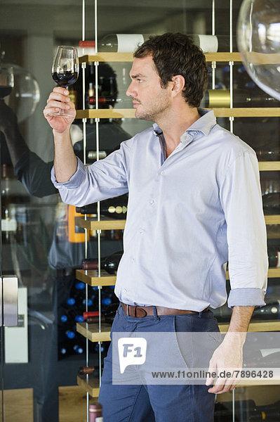 Mann schaut auf Rotwein im Weinglas