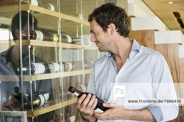 Lächelnder Mann mit einer Weinflasche