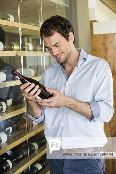 Lächelnder Mann beim Anblick einer Weinflasche
