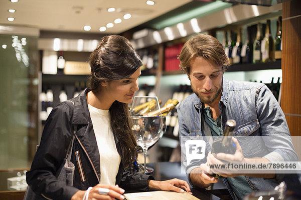 Verkäuferin  die einem Kunden eine Weinflasche zeigt