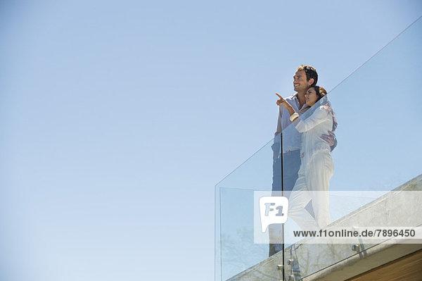 Paar steht zusammen auf einer Terrasse und zeigt weg.