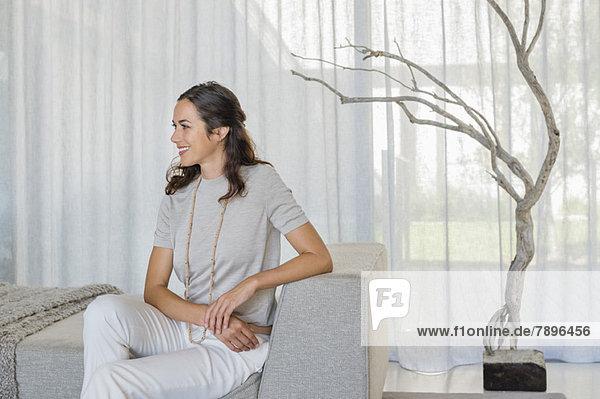 Schöne Frau auf einer Couch sitzend und lächelnd