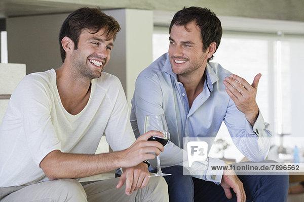 Lächelnde männliche Freunde mit Rotwein