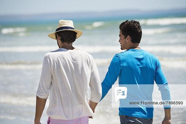 Zwei Männer  die am Strand spazieren gehen.