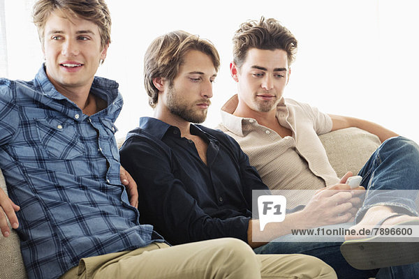 Drei männliche Freunde sitzen zusammen auf einer Couch.