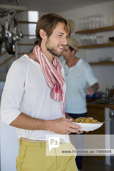 Mann  der einen Teller mit Essen trägt.