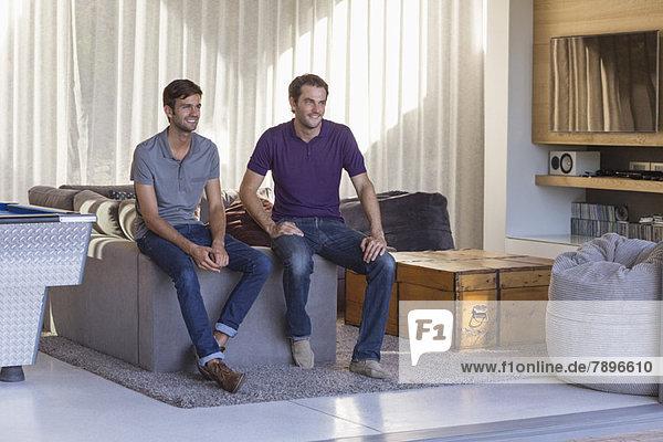 Zwei männliche Freunde lächeln zu Hause