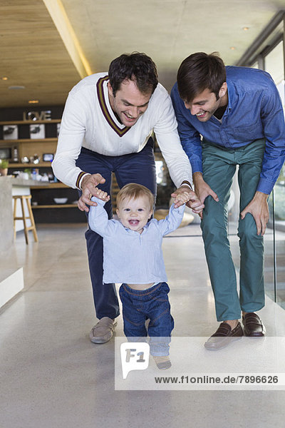 Eltern helfen ihrem Sohn beim Laufen